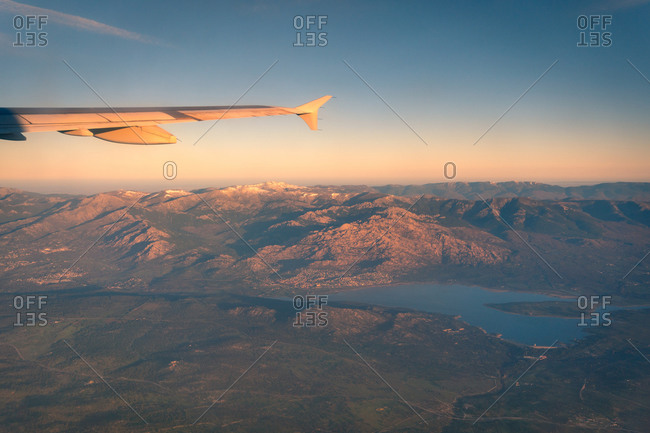 Spectacular view of wing of airplane flying over highland area during picturesque sunset in Gran Canaria