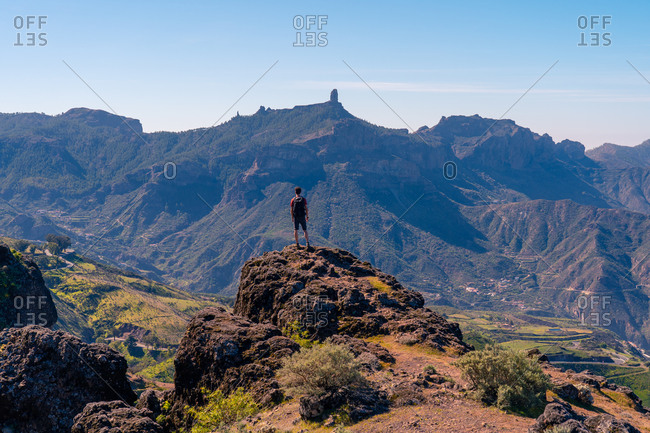 Back view of unrecognizable tourist standing on rough rock and enjoying breathtaking view of highland area in Gran Canaria
