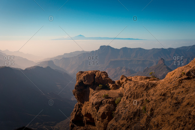 Wonderful scenery of rough highlands illuminated by sunset sun on background of amazing sky in Gran Canaria