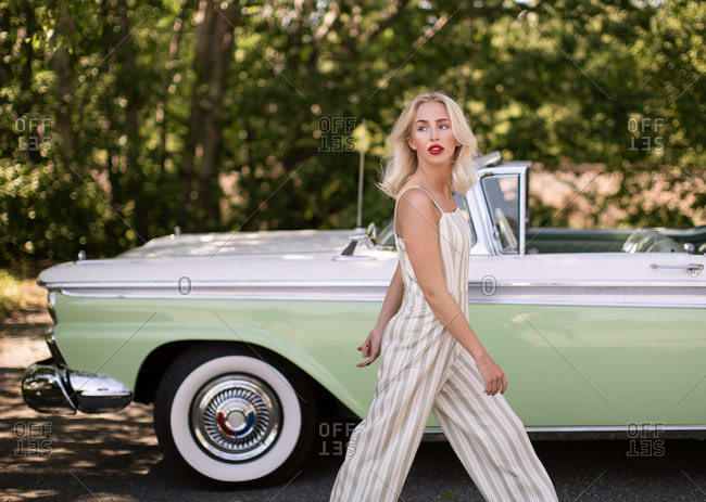 Side view of charming young blonde female in stylish outfit looking away while walking near old fashioned car in summer day