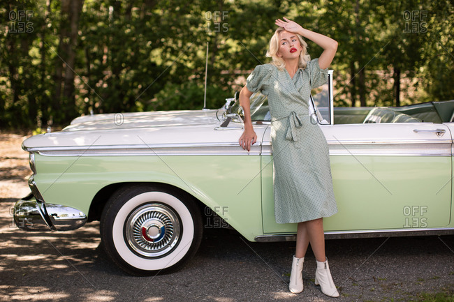 Young blonde female in stylish clothes with retro styled sunglasses leaning on vintage cabriolet parked near green trees in summer day looking away