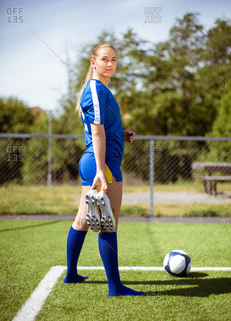 Side view of young sportswoman with boots standing on grassy field near ball and looking at camera over shoulder during football training on sunny day