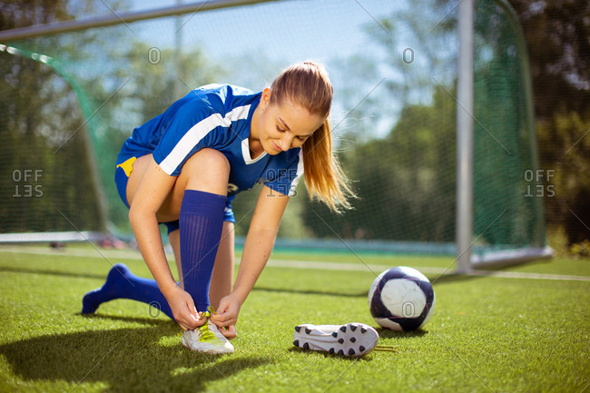 Glad female athlete putting on and tying boots near ball and goal while preparing for football training on field