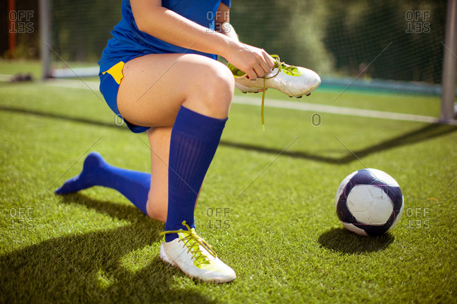 Crop female athlete putting on and tying boots near ball and goal while preparing for football training on field
