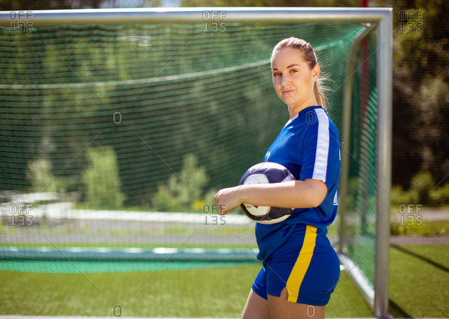 Side view of female football player with ball looking at camera while standing near goal during training on sunny day on field