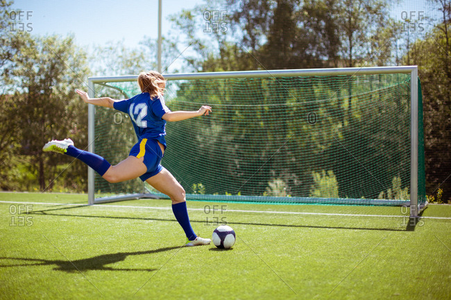 Side view of unrecognizable female athlete shooting ball into goal while playing football on field