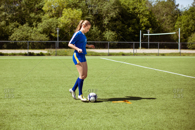 Young sportswoman standing on grassy field near ball and looking at camera over shoulder during football training on sunny day