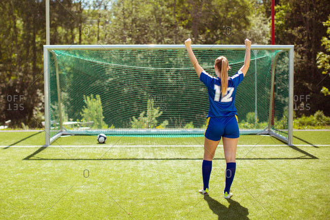 Back view of anonymous sportswoman raising fists and celebrating goal during football training on summer day