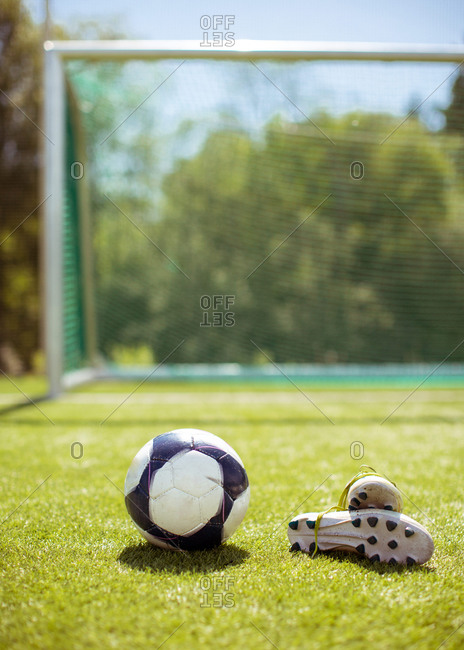 Boots and ball placed on green lawn near goal on summer day on football field