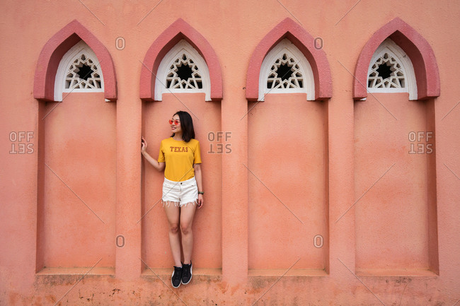 Full length of Asian female traveler standing in arched window of Pink Mosque while sightseeing in Kota Kinabalu during summer holiday and looking away
