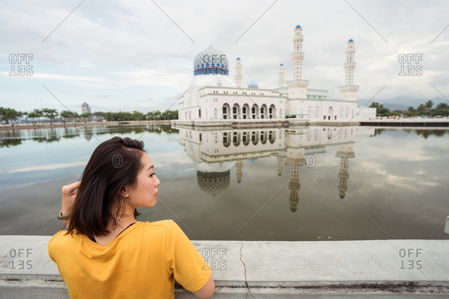 Back view of ethnic female tourist leaning on border near lake in front of famous Bandaraya Mosque and looking away during summer vacation in Kota Kinabalu