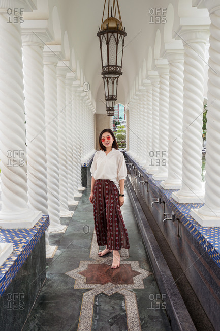 Full body of ethnic female traveler in summer outfit standing in ornamental walkway with stone columns of Omar Ali Saifuddien Mosque during holiday and looking at camera