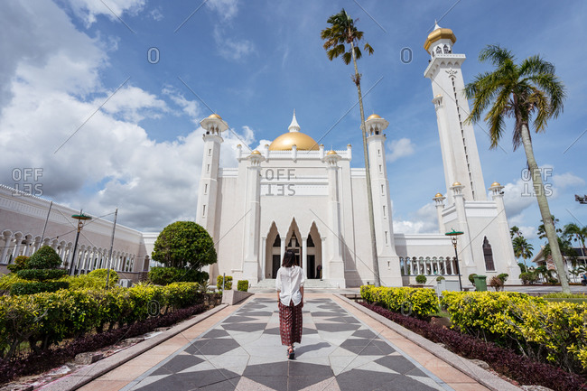 back view of unrecognizable female tourist standing on tiled path in front of Omar Ali Saifuddien Mosque and enjoying summer vacation in Bandar Seri Begawan
