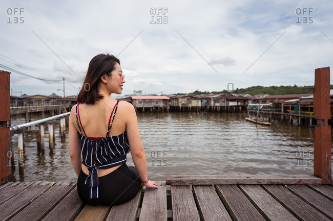 Back view of delighted ethnic female tourist relaxing on quay in Kampong Ayer floating village and looking away while enjoying holiday in Bandar Seri Begawan