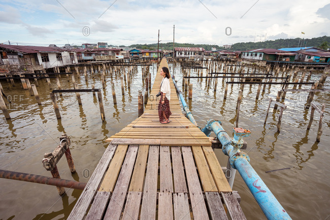 Side view of delighted ethnic female tourist relaxing on quay in Kampong Ayer floating village and looking away while enjoying holiday in Bandar Seri Begawan
