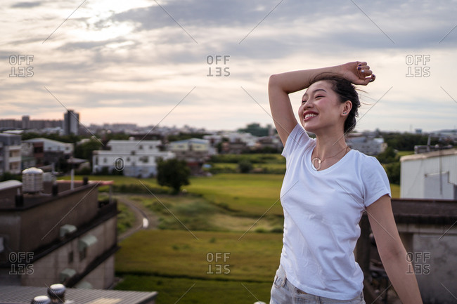 Side view of delighted ethnic female with raised arms smiling and stretching body against cloudy sunrise sky in morning