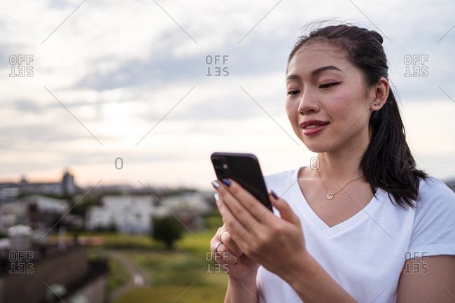 Woman selecting man while resting on terrace and browsing dating app on smartphone