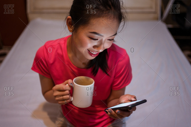 From above optimistic Asian woman with mug of hot drink smiling and reading message on smartphone while sitting on bed in evening at home