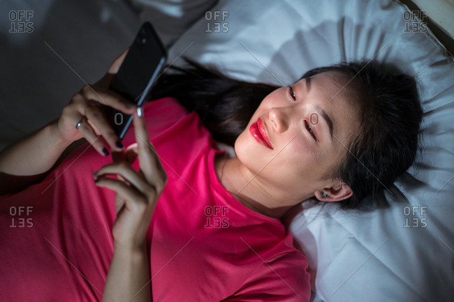 From above ethnic woman smiling and browsing dating app on smartphone while lying on bed in evening at home