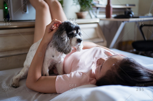 Young Asian woman resting on bed and caressing cute puppy on weekend day at home