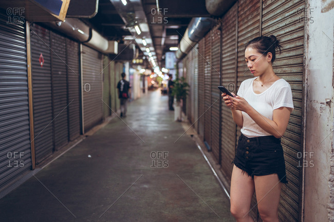Full body young Asian female in casual clothes with mobile phone in hand walking on narrow pedestrian underground pathway with closed shops in city