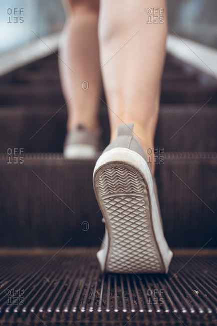 From below back view of crop unrecognizable female in casual sneakers going upstairs on escalator
