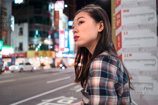 Side view of young Asian female in casual outfit looking away with hope while waiting for urban bus on bus stop in city during night time