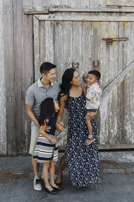 Parents with daughter and toddler boy in front of an old wooden barn