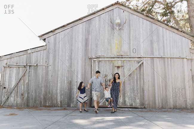 Mom and dad with daughter and toddler boy playing in front of a large barn