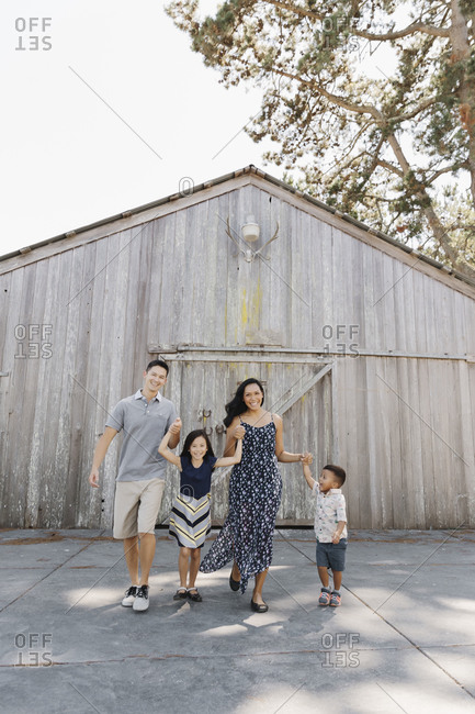 Parents and two kids holding hands and playing in front of a large barn
