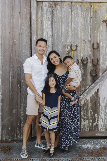 Beautiful family standing together in front of an old wooden barn