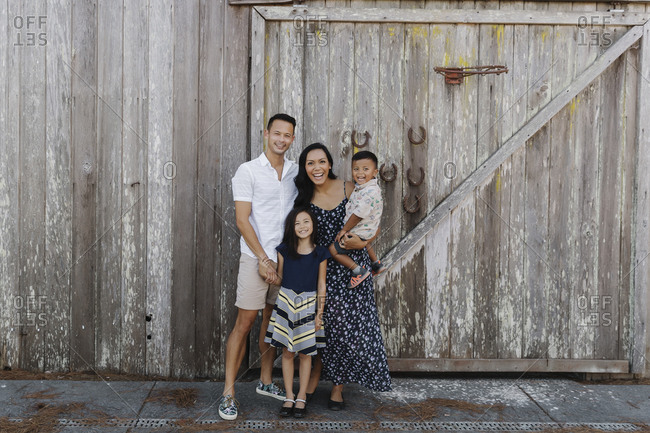 Portrait of a beautiful family standing together in front of an old wooden barn