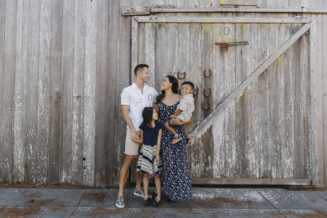 A happy young family standing together in front of an old wooden barn