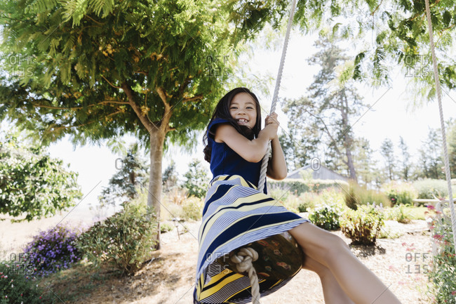 Girl swinging on tree swing rope