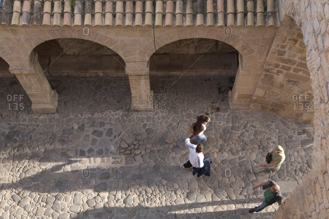Couples walking on cobbled street