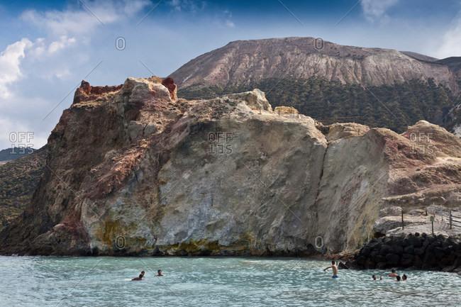 People swimming in ocean by cliffs