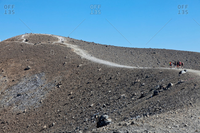 Hikers walking up rocky slope