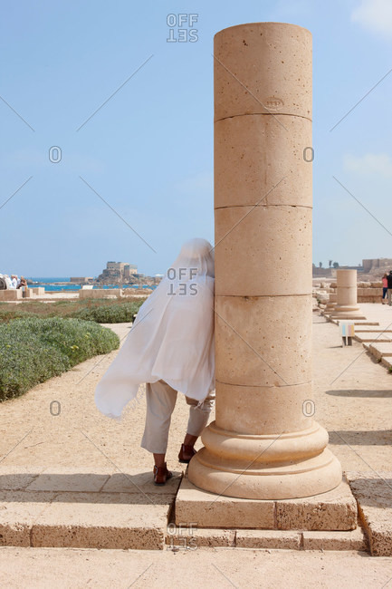 Person by column, roman ruins in ancient port city of Caesarea, Israel