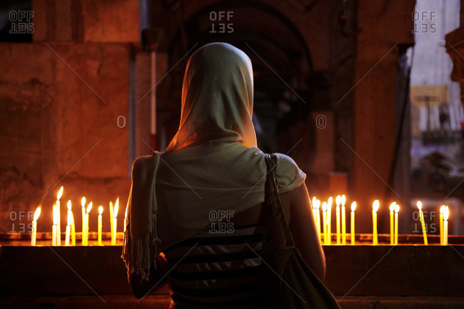 Woman in front of candles at Church of the Holy Sepulchre, Jerusalem, Israel