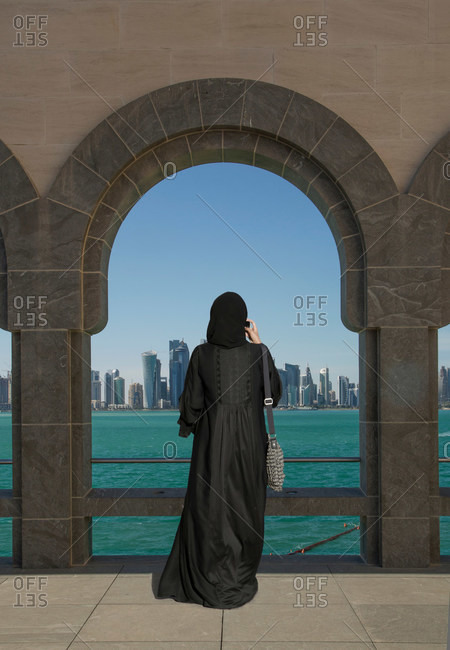 Arab woman taking pictures of skyline from the Museum of Islamic Art, Doha, Qatar
