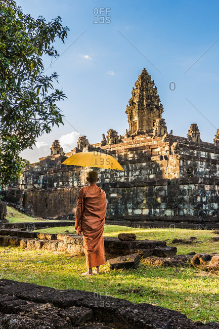 Monk with umbrella , Bakong Temple ruins (part of the Roluos Group of pre-Angkorian Hindu temples), Bakong, Cambodia