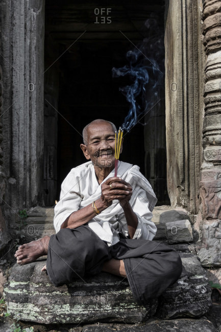 Devotee nun, lighting incense and offering prayers at Preah Khan Temple, Angkor, Cambodia
