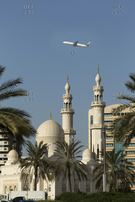 Dubai. Commercial jet flying over a Mosque