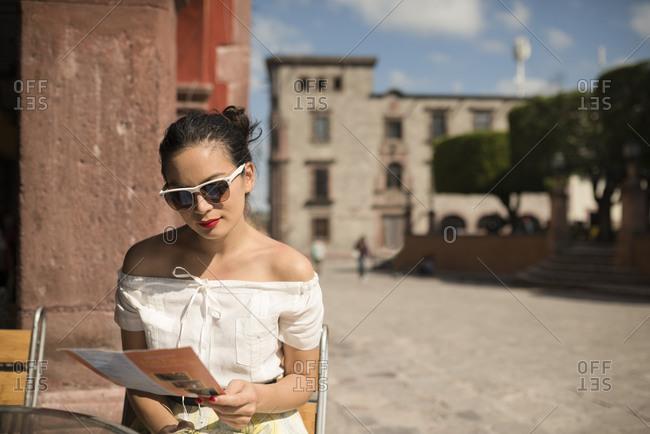 Female tourist reading menu at sidewalk cafe, San Miguel de Allende, Guanajuato, Mexico