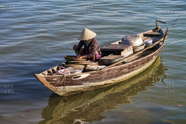 Fisherman sitting on boat in river, Hoi An, Vietnam