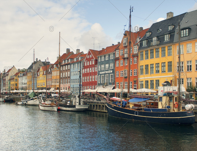 Sailing boats, sidewalk restaurants and colorful townhouses, Nyhavn harbor, Copenhagen, Denmark
