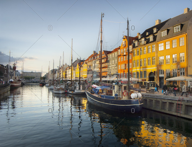 Sailing boats, sidewalk restaurants and colorful townhouses at Nyhavn harbor, Copenhagen, Denmark