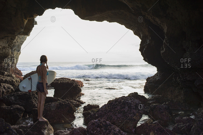 Woman standing on rocks by cove, holding surfboard, Nusa Ceningan, Indonesia