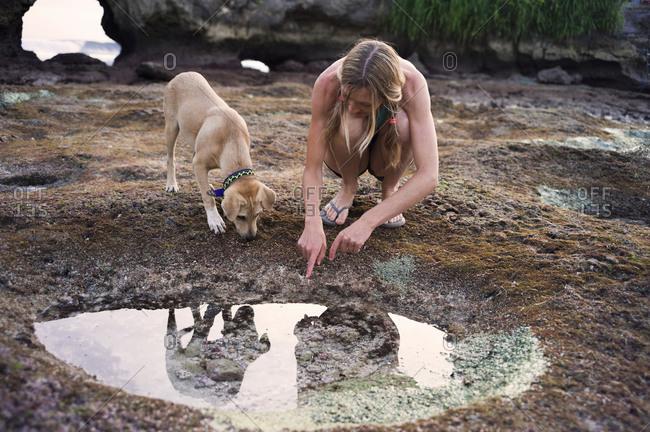 Woman looking in rock pool, dog beside her, Nusa Ceningan, Indonesia