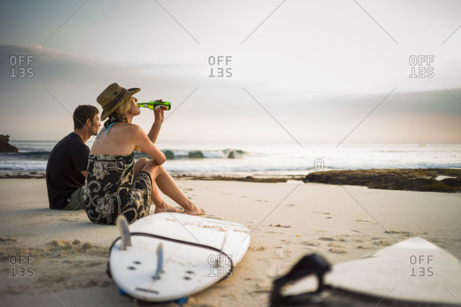 Couple sitting on beach with surfboards, looking out to sea, Nusa Lembongan, Indonesia